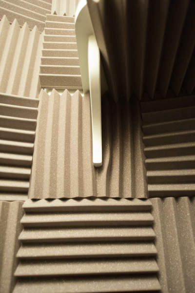 Acoustic foam tiles showing one tile cut to accommodate shelf support