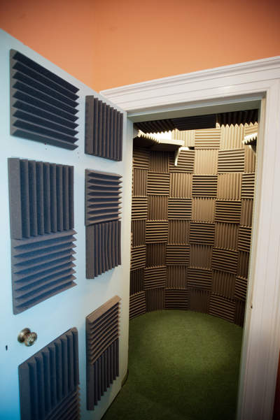 Empty vocal booth - open door on left, with acoustic tiles, walls of booth covered with tiles.
