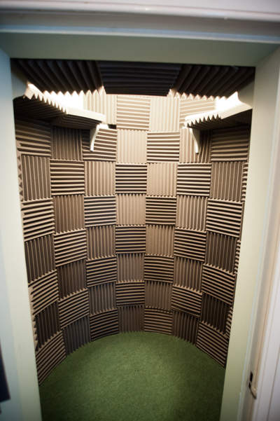 Vocal booth with acoustic tiles seen through doorway