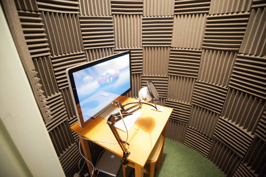 Finished vocal booth showing microphone on arm, table and monitor in front of wall with acoustic tiles.