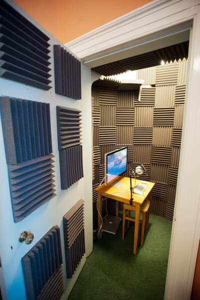 Table with screen, microphone keyboard and mouse in the vocal booth seen through open door.