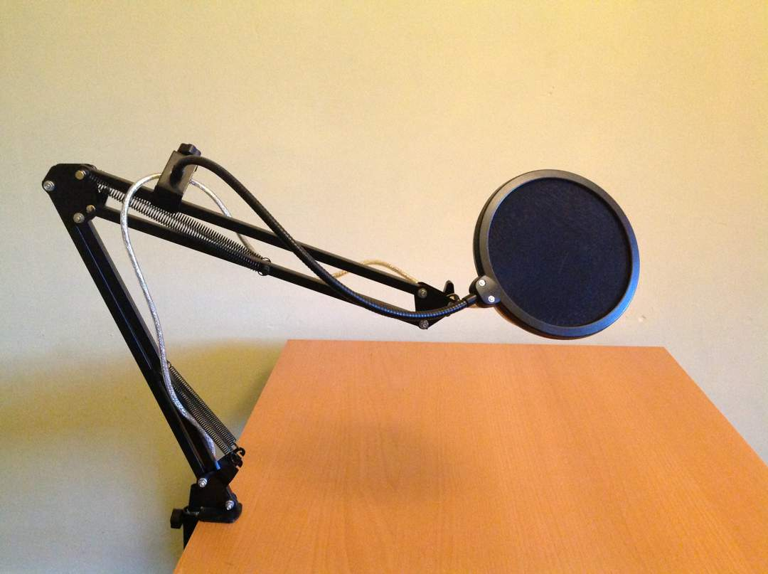 Microphone arm with black circular pop filter.