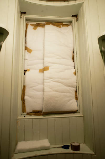 Window covered with white insulation held in place with brown parcel tape
