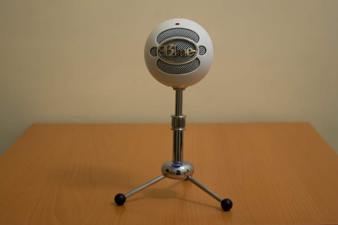 Blue Snowball Microphone on small tripod stand.