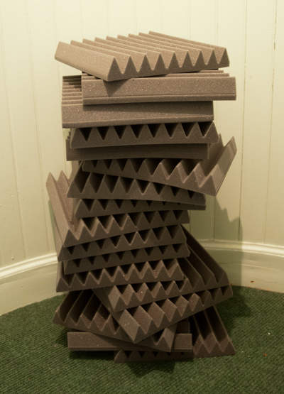Stack of grey acoustic tiles on a green carpet