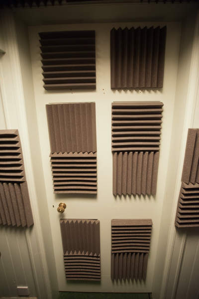 Closed door with 10 acoustic foam tiles attached to it in checkerboard pattern