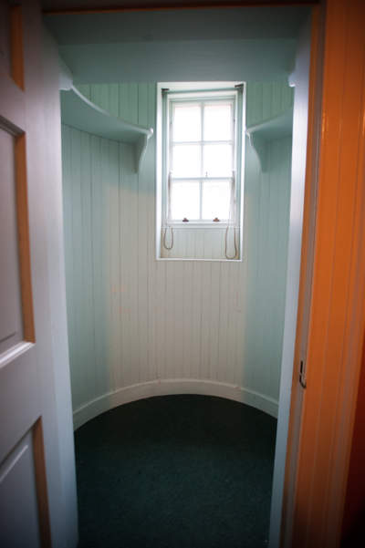 Empty semi-circular closet photographed from the doorway - there is a window in the closet facing the camera.
