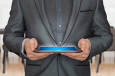 Man wearing a suit and using a tablet - picture is cropped and doesn't show his head