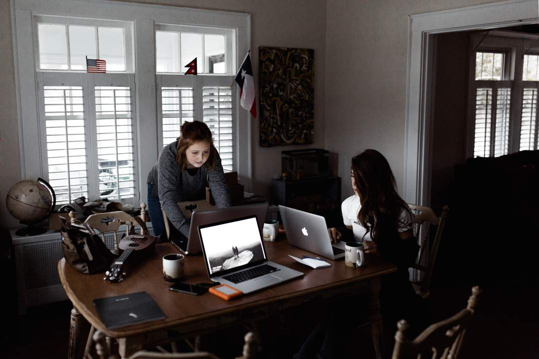 Two women at table with laptop computers - window with shutters in background