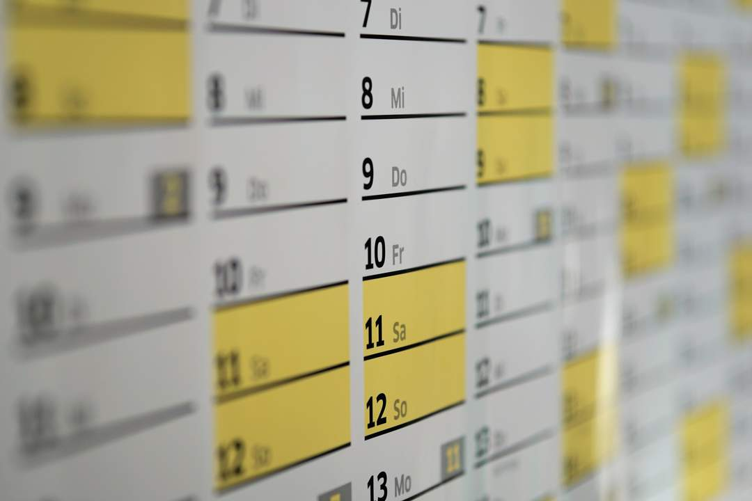 Photo of calendar showing weekend days highlighted in yellow. Depth of field is narrow so only the centre of the photo is sharp with the left and right out of focus