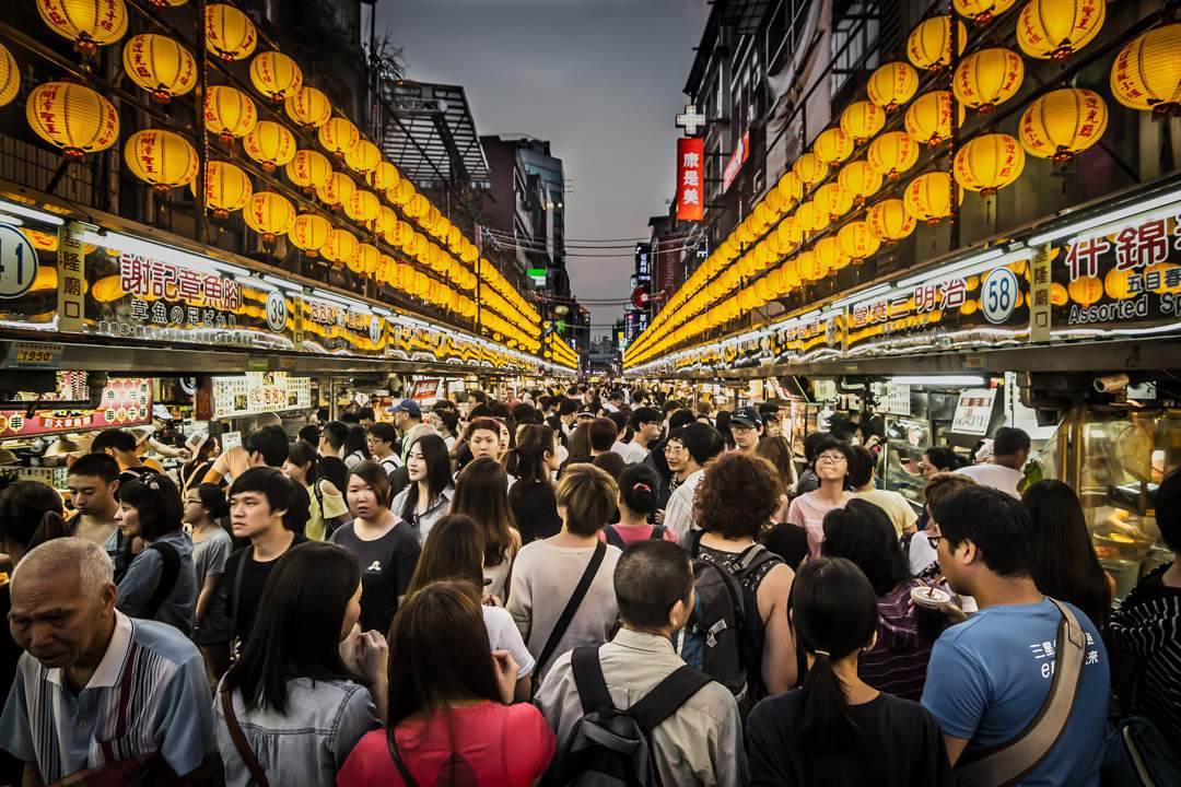 Crowd of people in night market - two lines of yellow lanterns recede into the distance