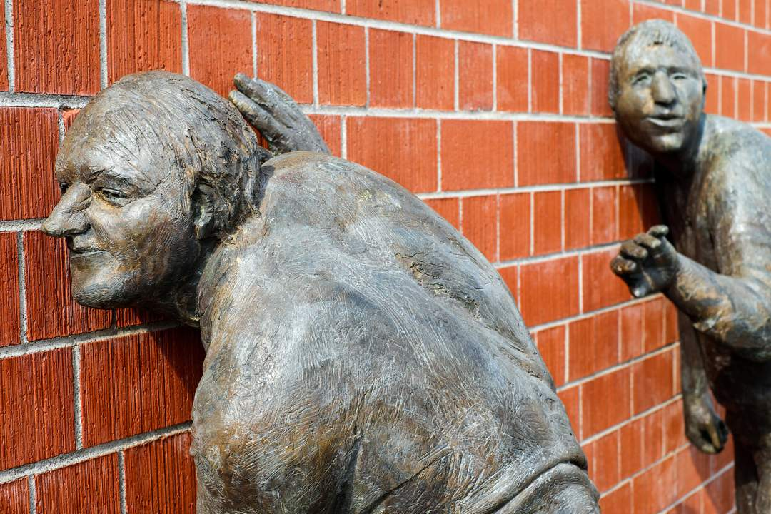 Two statues of men with their ears pressed against a brick wall.