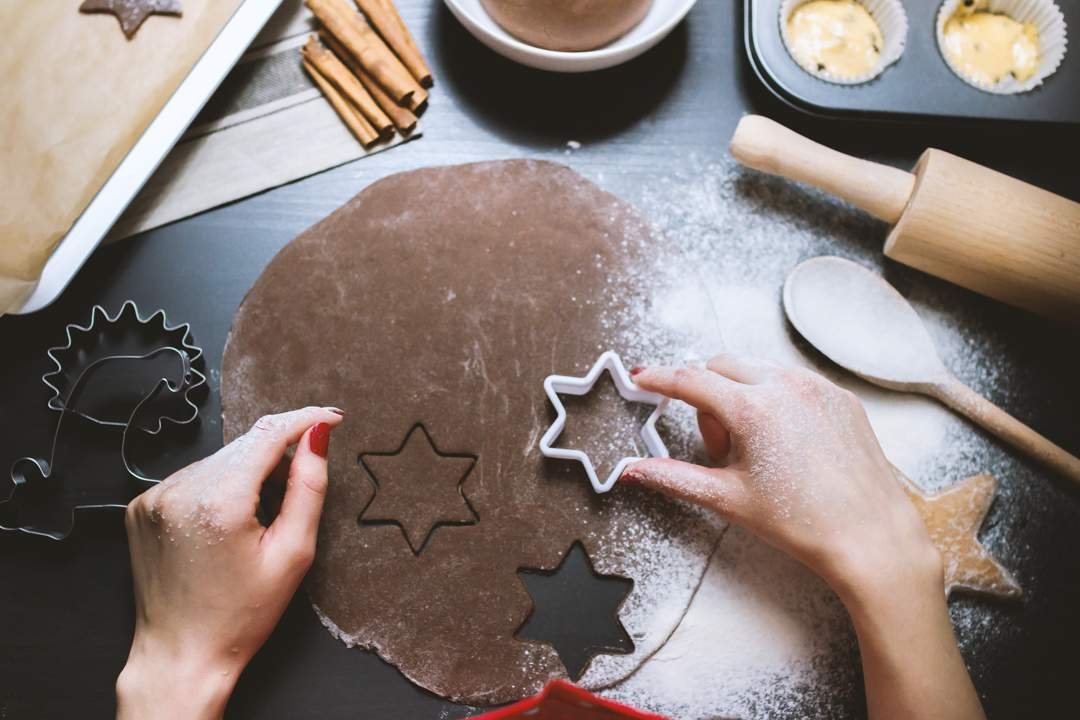 Woman's hands cutting out star shapes from chocolate dough with a cookie cutter