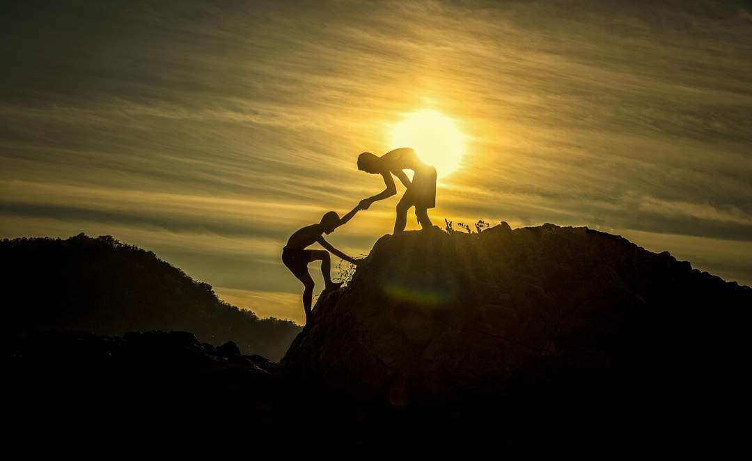 Two people silhoutted agains the sunset - one is helping the other climb onto a rock