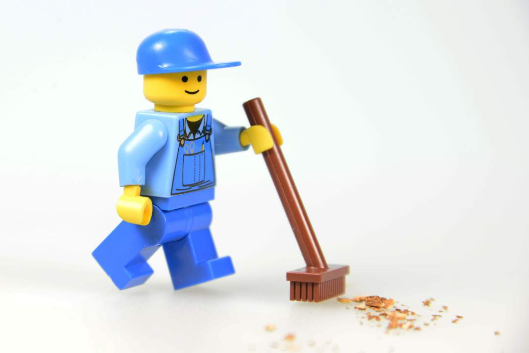 Toy Lego Figure dressed in blue. holding brush and sweeping up