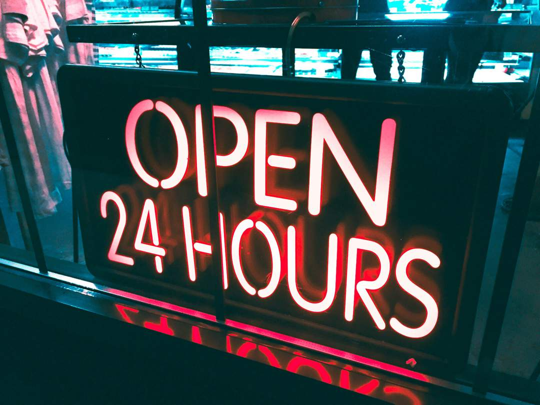 Red neon sign in shop window that says Open 24 Hours.