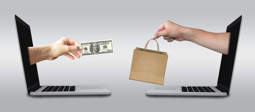 Two laptops facing each other, each with a hand coming out of the screen. The left hand one is holding a $100 bill, the right hand one is holding a brown paper shopping bag.
