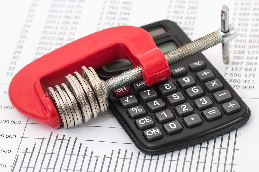 Background is paper with figures and graph - there's a black calculator sitting on the paper and a red G clamp clamping a stack of coins sitting on top of the calculator.