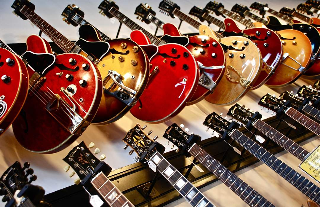 Looking up at two rows of electric guitars handing on the wall of a shop.