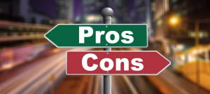 "Green sign with word ""Pros"" pointing left and red sign with word ""Cons"" pointing right - in front of blurred background of city at night."