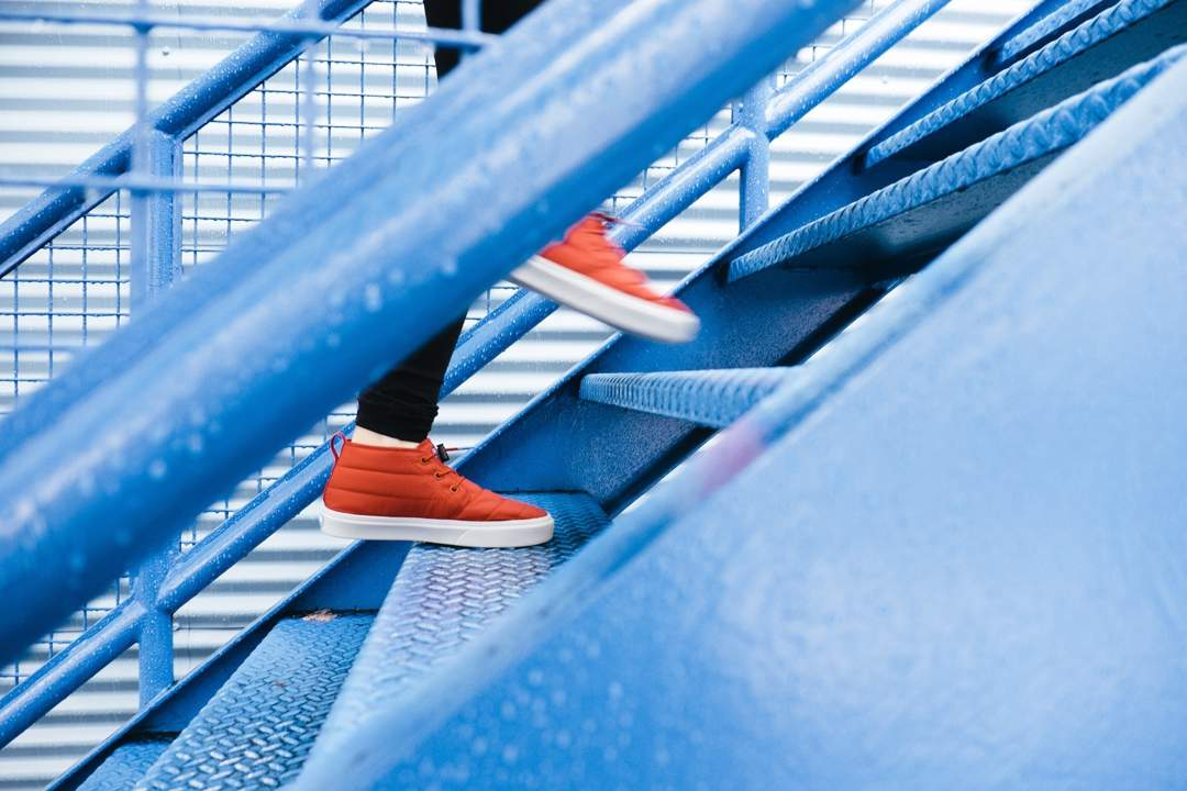 Legs of person wearing red trainers climbing from left to right up blue metal stairs.