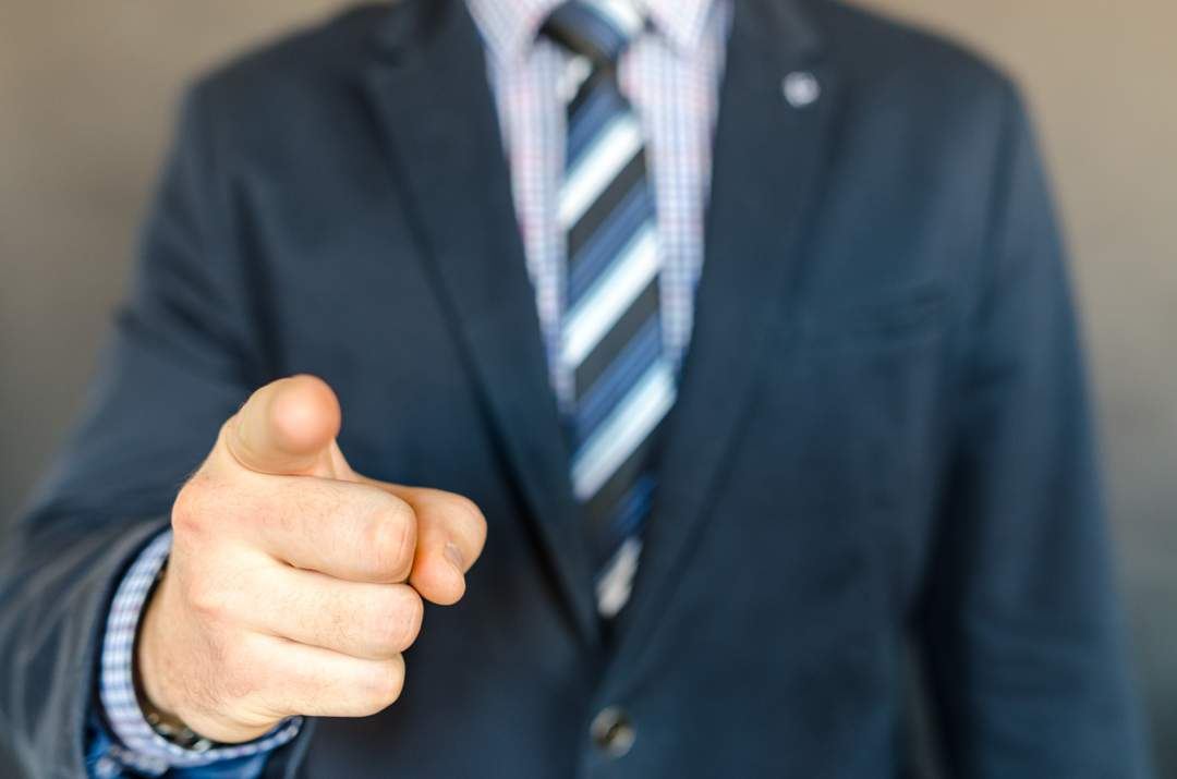 Out of focus torso of man in business suit with checked shirt and striped tie - he is pointing at the viewer with his right hand which is in focus.