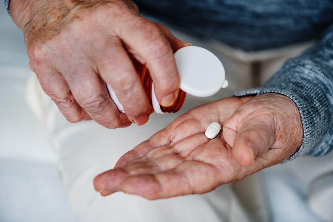 Hands of elderly man with pill bottle in one hand and two pills in the other.