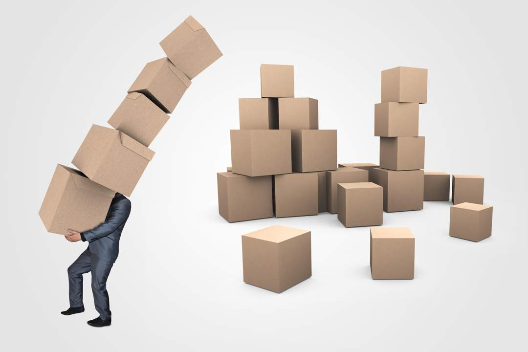 Man in suit staggering under weight of huge pile of boxes toppling over while more piles of boxes cover the floor