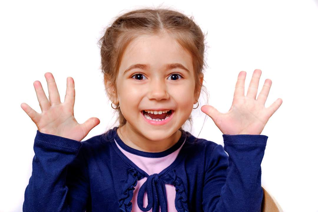 Little girl in blue top holding both hands up with expression of delight on her face.