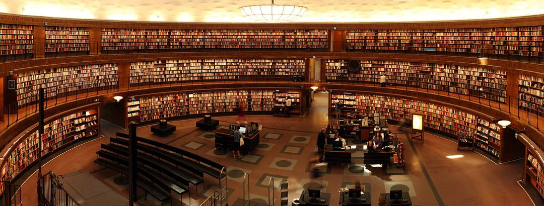 Large circular library with three floors of bookshelves around a central atrium with reading desks.