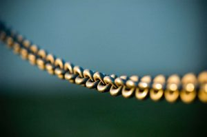 Links of a metal chain looking golden in evening sunlight against a blurred blue background.