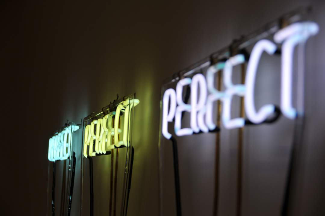 "Three neon signs each one spelling out the word ""perfect"""