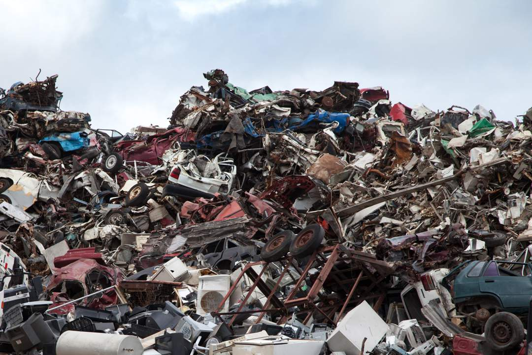 Scrapyard showing piles of old cars, domestic appliances and other scrap metal.