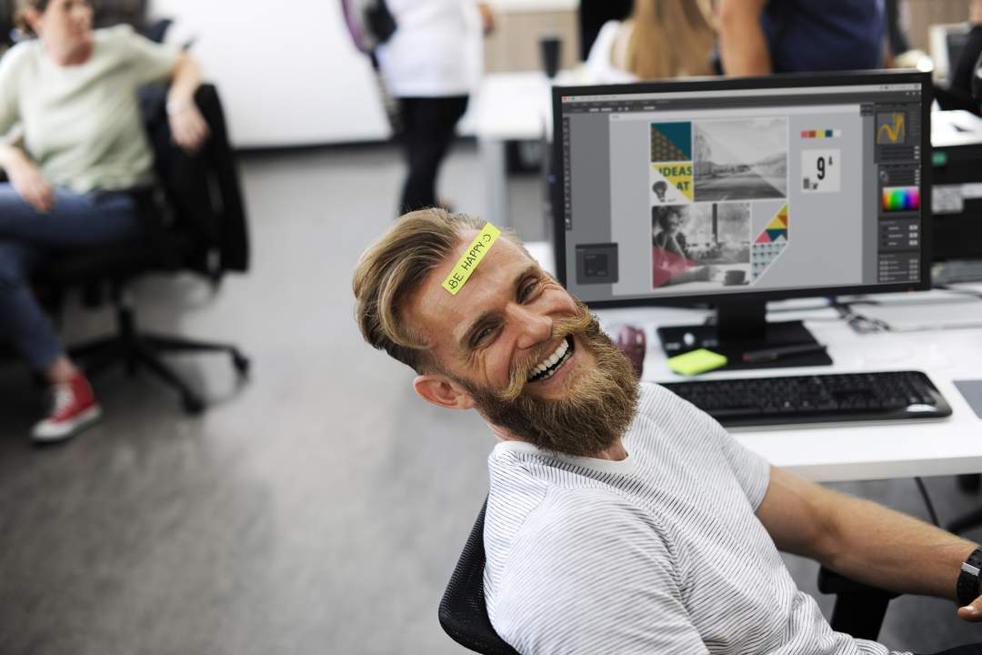 "Bearded man at his office desk, leaning back in his chair and laughing - he has a sticker on his forehead that says ""Be Happy""."