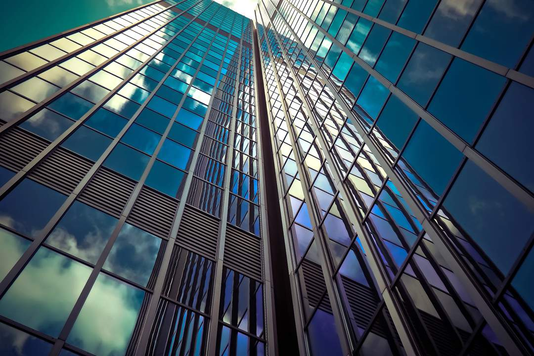 Glass skyscraper viewed from ground reflecting blue sky and clouds.