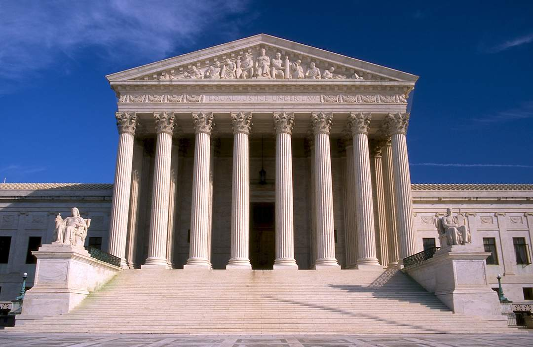 "US Supreme Court building against a blue sky. Carved roof with the words ""Equal Justice for All"" is supported by 8 stone pillars - the building is at the top of a large flight of steps."