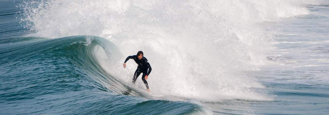 Man in black wetsuit surfing a large breaking wave.