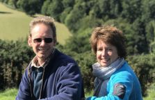 Quenton and Clare smiling and sitting in front of a lovely countryside view.