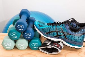 Collection of blue gym equipment including dumbbells, a trainer and a gym ball